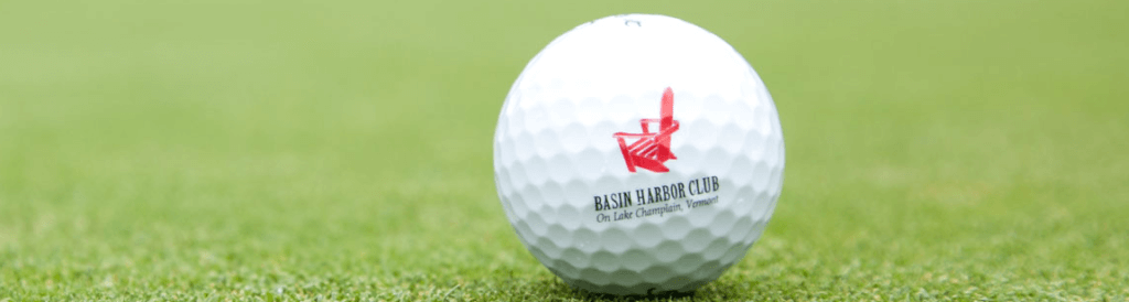 Basin Harbor branded golf ball resting on a green