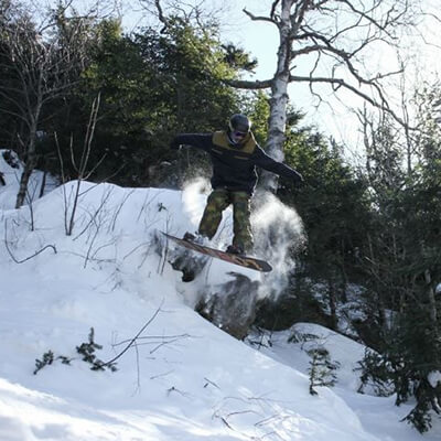 Bolton Valley snowboarder jumping off a cliff in the back country