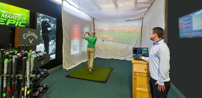 man swinging a golf club in an indoor demo area
