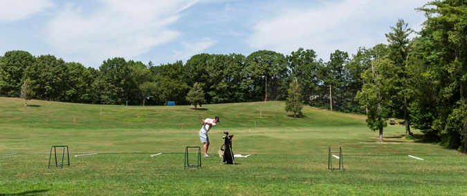 person swinging a golf club on an outdoor range, view from behind