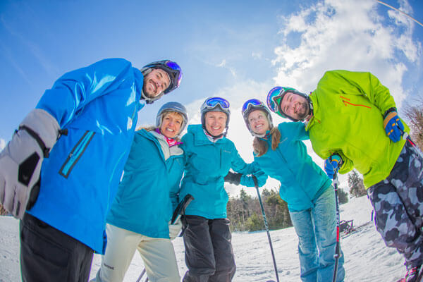 group of happy adults dressed in winter clothes leaning over the camera and smiling