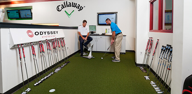 Man putting a golf ball towards a hole in the Callaway PuttLab