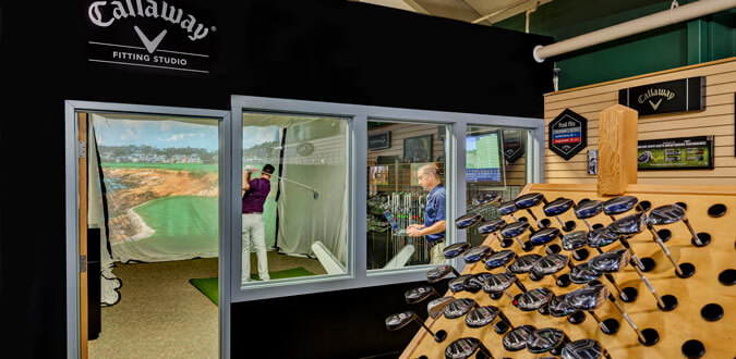 indoor golf fitting studio with a rack of golf clubs in the foreground and a man swinging a club in the background