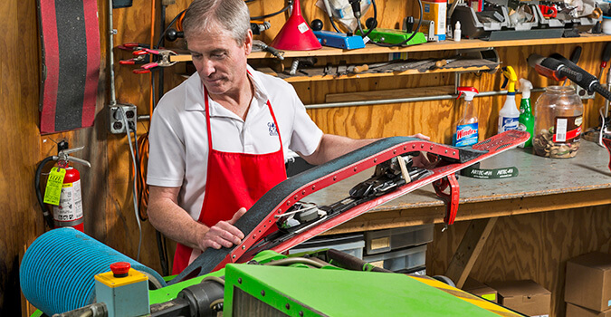 Employee in repair shop sharpening a ski through the machine