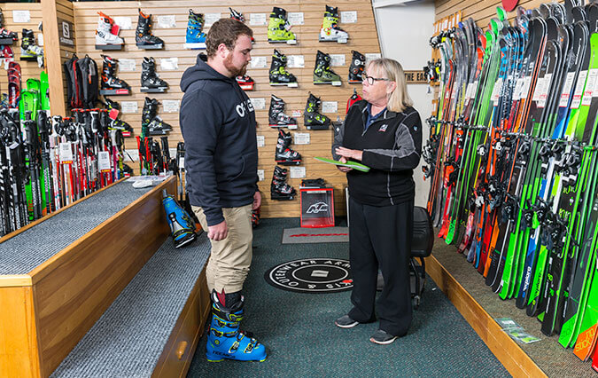 Store employee helping customer get properly fit in a ski boot