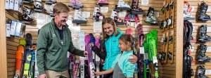 Mother and daughter receiving guidance from store employee in selecting a pair of skis