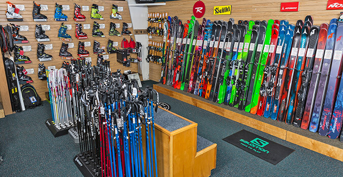 Wall of skis and ski poles and ski boots