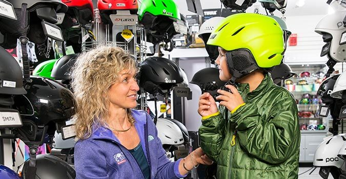Woman helping a child properly fit a ski helmet