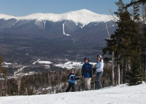 Family of skiers standing on slope with view of Mount Washington behind them