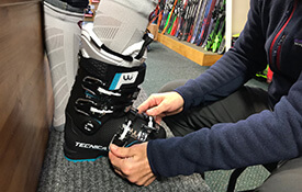 Customer's foot inside a ski boot with employee buckling boot straps