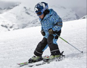 Young boy snow plowing down ski slope