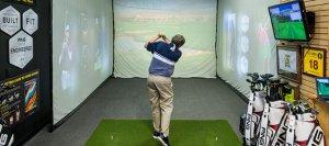Man swinging golf club inside a fitting bay