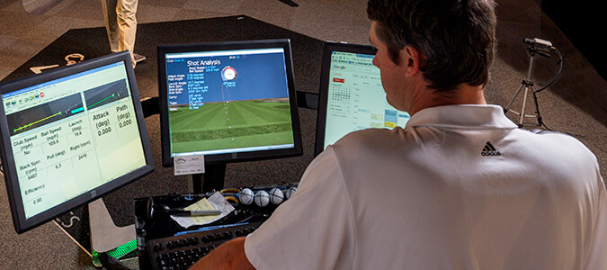 Man looking at screen of results from golf swing