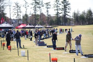Group of golfers at a driving range trying different clubs at a demo event