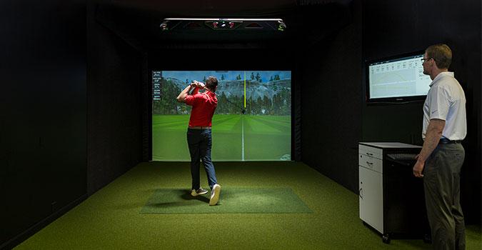 Man swinging a club in a GC Hawk simulator
